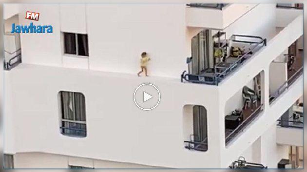 Une fillette filmée en train de marcher sur le rebord d'un immeuble